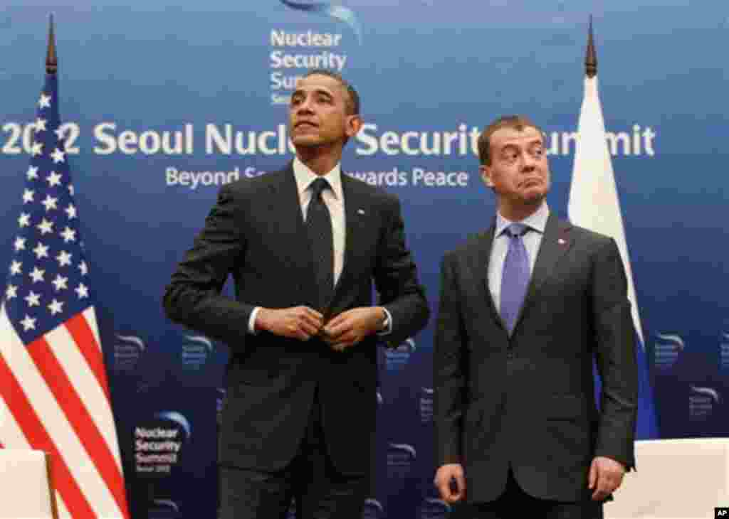 U.S. President Barack Obama, left, and Russian President Dmitry Medvedev stand together at the end of a bilateral meeting at the Nuclear Security Summit in Seoul, South Korea, Monday, March 26, 2012. (AP Photo/Pablo Martinez Monsivais)