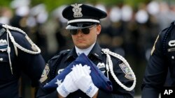 FILE - A member of a police honor guard carries an American flag after funeral services for Baton Rouge Police Officer Matthew Gerald at the Healing Place Church in Baton Rouge, La., July 22, 2016.
