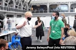 Perdana Menteri Inggris Boris Johnson berbincang dengan sejumlah warga saat mengunjungi pusat vaksinasi COVID-19 di Business Design Centre di Islington, London, Inggris, 18 Mei 2021. (Foto: Jeremy Selwyn/Pool via Reuters)