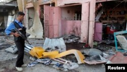 Một cảnh sát rà soát hiện trường vụ tấn công bằng bom ở Kirkuk, 25/5/2014.