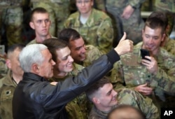 U.S. Vice President Mike Pence poses for photos with troops at Bagram Air Base in Afghanistan, Dec. 21, 2017.