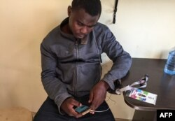 Ismail Olamilekan, a 21-year-old young Nigerian, sits in his room at a hostel in Moscow, July 12, 2018.