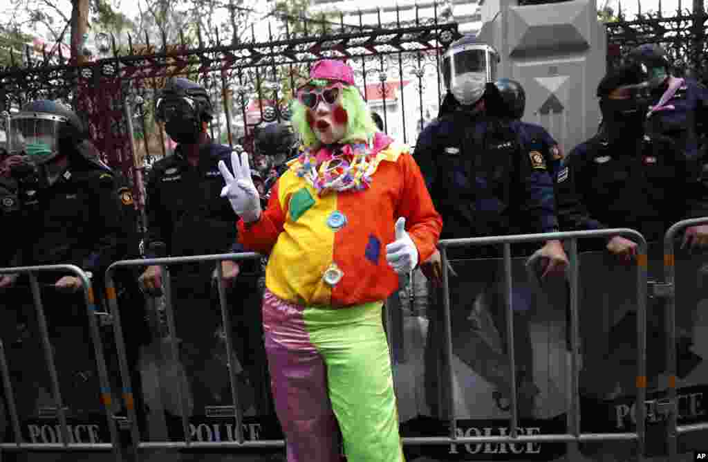 A pro-democracy protester wearing a clown costume raises a three-finger salute in front of riot police at Police Headquarter in Bangkok, Thailand. Protesters gathered to call for fairness for low-ranking police.