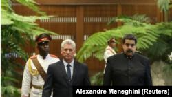 Los presidentes de Cuba, Miguel Díaz-Canel (izq), y Venezuela, Nicolás Maduro, pasan revista a la guardia de honor durante una ceremonia en el Palacio de la Revolución en La Habana. 21 abril 2018.