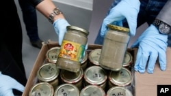 FILE - Investigators display confiscated jars filled with heroin at the headquarters of the federal police in Wiesbaden, Germany, Oct. 9, 2014.