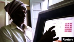 FILE - An Indian farmer uses a computer to check land records in Ramanagaram, in the southern state of Karnataka, May 26, 2001. Land records in most Indian states date to the colonial era, and most land holdings have uncertain ownership. Fraud is rampant.