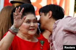 FILE - Philippines Vice-Presidential candidate BongBong Marcos whispers to his mother, former First Lady and Congresswoman Imelda Marcos, before BongBong announced his candidacy in Manila Philippines, October 10, 2015.
