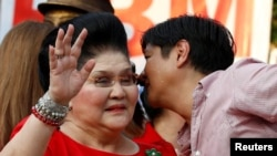"""Philippines vice-presidential candidate Ferdinand """"BongBong"""" Marcos, Jr. whispers to his mother, former First Lady and Congresswoman Imelda Marcos, before BongBong announced his candidacy in Manila, October 10, 2015."""