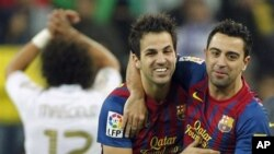 FC Barcelona's Cesc Fabregas, center, celebrates with Xavi Hernandez, right, during the Spanish La Liga soccer match against Real Madrid at the Santiago Bernabeu stadium in Madrid, Spain.