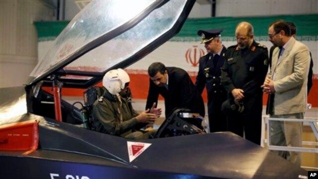 Presiden Iran Mahmoud Ahmadinejad mendengarkan penjelasan pilot pesawat jet tempur Qaher. (Foto: AP)