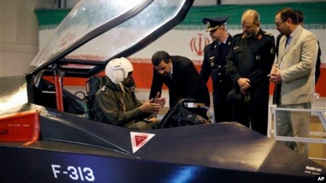 Presiden Iran Mahmoud Ahmadinejad (tengah) mendengarkan katerangan dari seorang pilot dalam upacara peluncuran pesawat jet tempur baru buatan Iran, Qaher-313, atau disebut juga Dominant-313,di Teheran, Iran, 2 Februari 2013. (AP Photo/Mehr News Agency, Younes Khani)