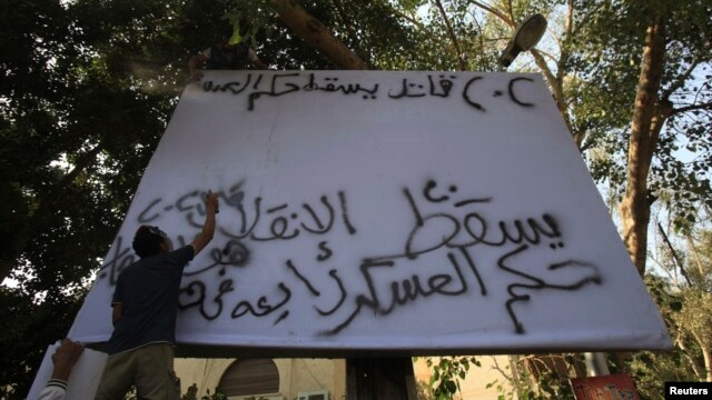 """Supporters of the Muslim Brotherhood and ousted Egyptian President Mohamed Mursi spray """"Down with military rule - Sisi killer"""" on a billboard during a protest against the military and interior ministry in the fashionable Maadi suburb in Cairo, November 1,"""