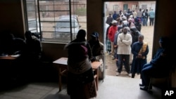 FILE: Zimbabweans queue to cast their votes in the country's general elections in Morondera, rural Zimbabwe, July 31, 2013.