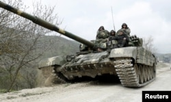 FILE - A tank of the self-defense army of Nagorno-Karabakh moves on the road near the village of Mataghis, April 6, 2016.