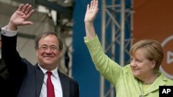 German Chancellor Angela Merkel and Armin Laschet, the North Rhine-Westphalia top candidate of her Christian Democrats, wave to supporters at the last stage of the state election campaign in Aachen, Germany, May 13, 2017. Germany's most populous state is holding an election Sunday that serves as a prelude to a national vote four months away, and could give Merkel new momentum in her quest for a fourth term.