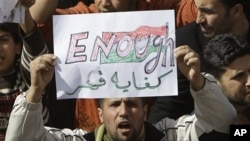 A Libyan protester holds up a sign against Libyan Leader Moammar Gadhafi during a demonstration, in Tobruk, Libya, February 23, 2011.