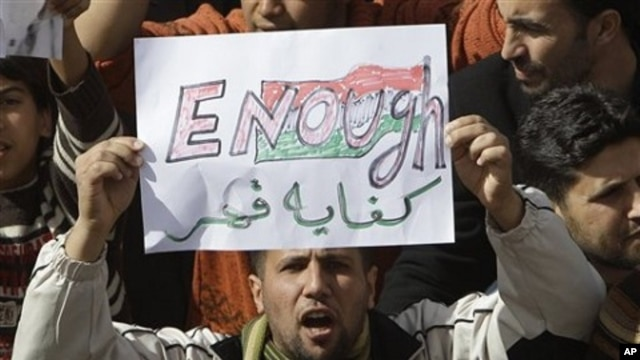 A Libyan protester holds up a sign against Libyan leader Moammar Gadhafi during a demonstration in Tobruk, Libya, February 23, 2011