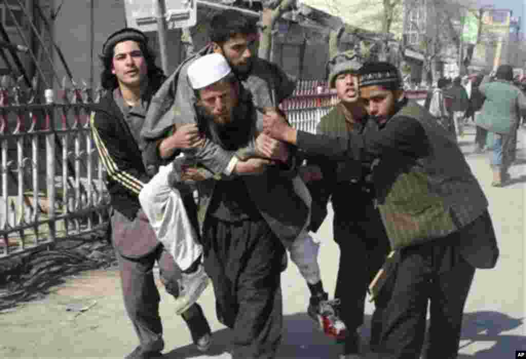 Afghans carry a wounded man during an anti-U.S. demonstration in Kunduz, north of Kabul, Afghanistan, Saturday, Feb. 25, 2012.