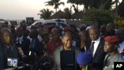 Ivory Coast's President Alassane Ouattara, center, visits the area where gunmen attacked people in Grand Bassam, Ivory Coast, March 13, 2016.