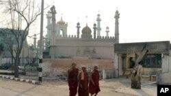 Tiga biksu Budha melintasi jalan di dekat sebuah masjid di Meikhtila, sekitar 550 kilometer sebelah utara Rangoon, Burma (Foto: dok). Kepolisian Burma telah menangkap sedikitnya 42 orang dan diperkirakan akan segera diadili dalam kekerasan sektarian di wilayah ini (4/4).