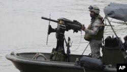 Soldados de la Armada colombiana patrullan el río Arauca, la frontera natural con Venezuela, visto desde Arauquita, Colombia, el viernes 26 de marzo de 2021.