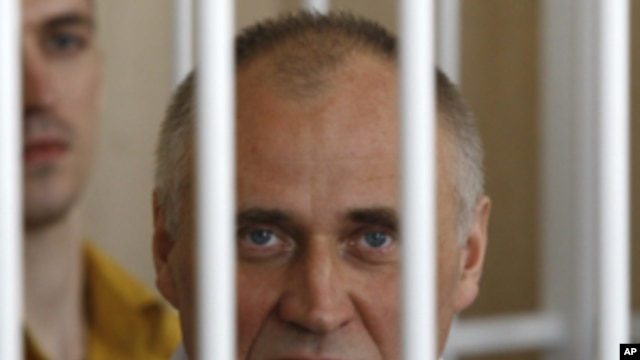 A former opposition presidential candidate Nikolai Statkevich sits in a cage during a court session in Minsk, Belarus, Thursday, May 26, 2011