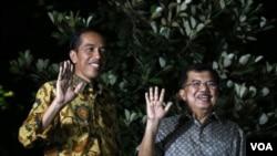 ປະທານາທິບໍດີ ທີ່ໄດ້ຮັບເລືອກໃໝ່ ຂອງອິນໂດເນເຊຍ ທ່ານ Joko Widodo (ຊ້າຍ) ແລະຄູ່ຮ່ວມງານ ທ່ານ Jusuf Kalla ໂບກມືແກ່ບັນດານັກຂ່າວ.