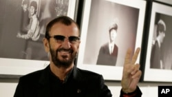 Pop icon and former Beatle Ringo Starr poses for the media in front of some of his photographs during a photocall as he launches a book called 'Photograph' in London, Sept. 9, 2015.