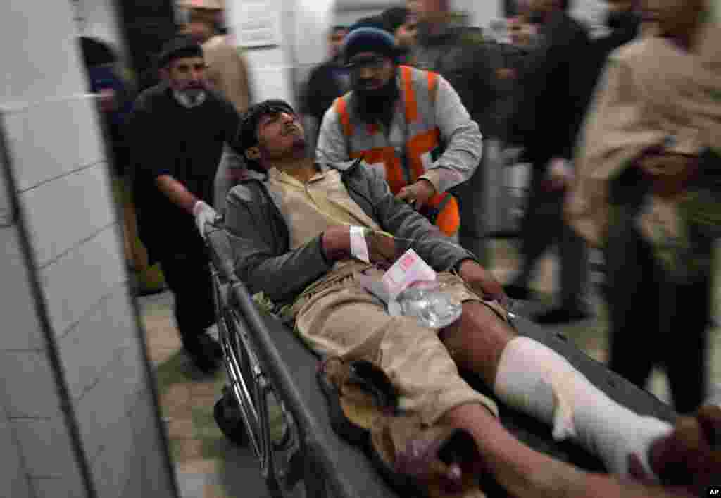 A man who was injured in an explosion at a movie theater is brought to a hospital for treatment in Peshawar, Pakistan, Feb. 2, 2014.