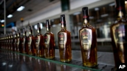 "FILE - Bottles of Santa Teresa ""Gran Reserva"" rum move along the assembly line at the factory in La Victoria, Aragua State, Venezuela, March 26, 2015."