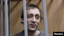 Dancer Pavel Dmitrichenko looks out from the defendant's holding cell during a hearing in Moscow on October 22, 2013. Dmitrichenko, who made his name on stage at Moscow's Bolshoi Theatre, went on trial on Tuesday for an acid attack that nearly blinded the ballet's artistic director.