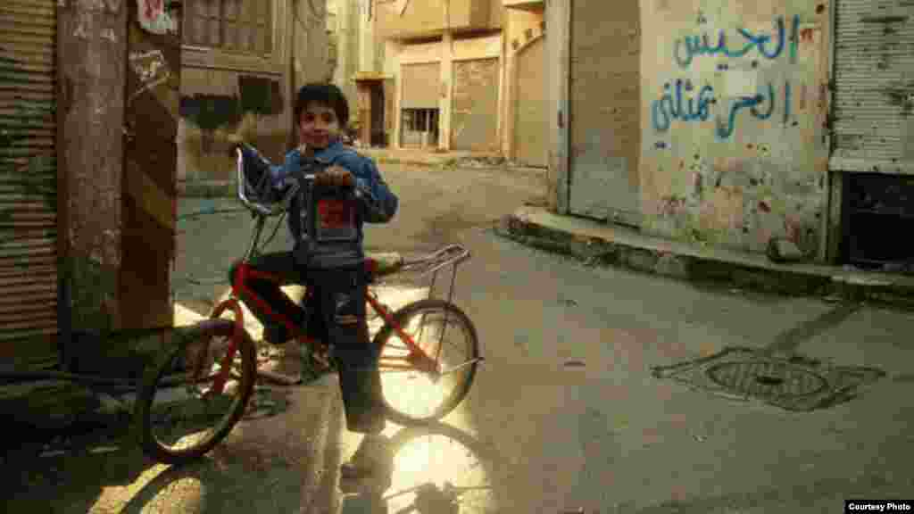 Yaseen on bicycle 30 minutes before a Syrian rocket from a government-held position exploded, killing he and his sister, Maryam, January 20, 2013 (Lens Young Homsi)