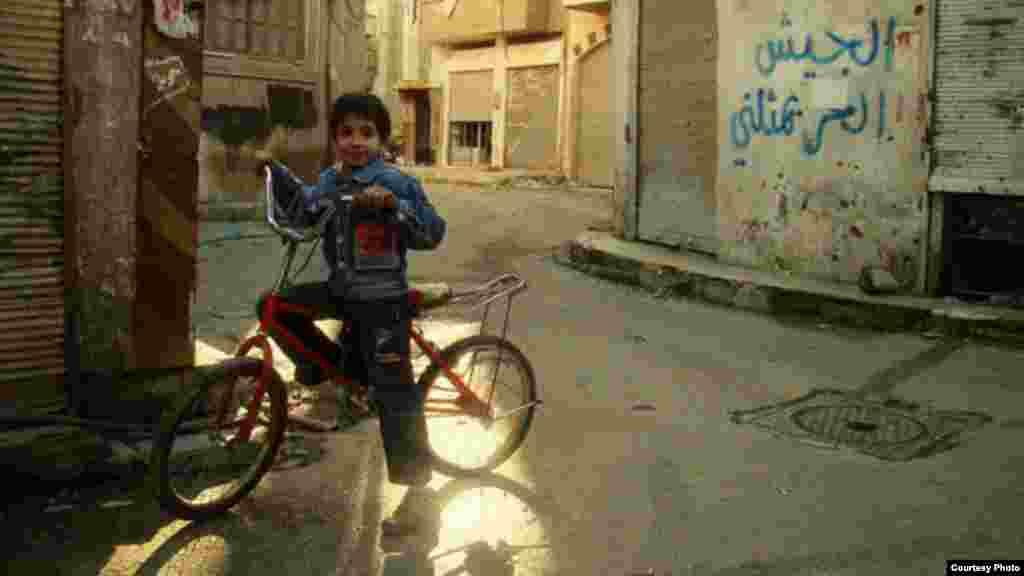 Một bé trai Syria đạp xe tại thành phố Homs. 30 phút sau khi chụp ảnh, một tên lửa của chính phủ Syria đã đánh trúng khu vực giết chết cậu bé và em gái, ngày 20/1/2013.
