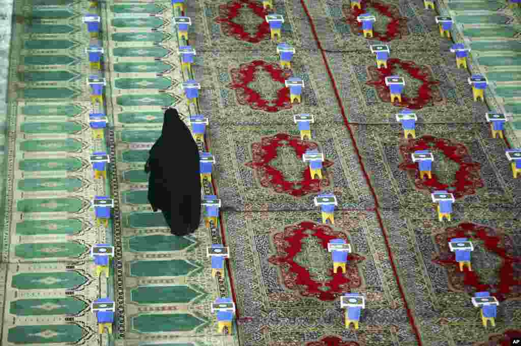 An Iranian woman makes her way between copies of the Quran, Islam's holy book, prepared for a ceremony during Ramadan at the shrine of Saint Mohammad Helal Ibn Ali in the city of Aran and Bidgol, some 140 miles (225 kilometers) south Tehran.