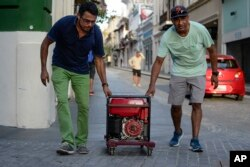 In this Oct. 20, 2017, photo, men push a generator along Fortaleza street, one month after Hurricane Maria hit San Juan, Puerto Rico.
