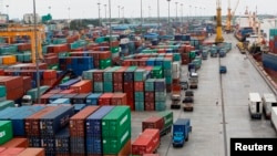 FILE - Workers are seen among the containers at Asia World port in Yangon, July 2, 2014. During a recent conference, American and Myanmar businesses exchanged views on how to develop economic ties between the two nations despite challenges in the financial sector and poor infrastructure.