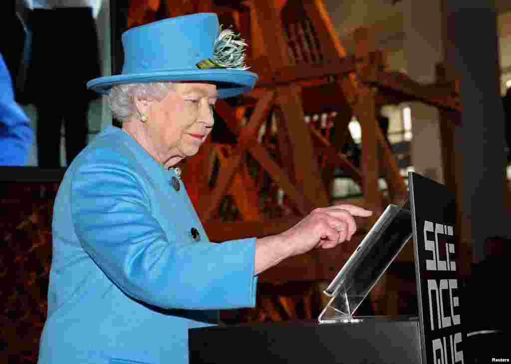Britain's Queen Elizabeth presses a button to send her first Tweet during a visit to the 'Information Age' Exhibition at the Science Museum in London.