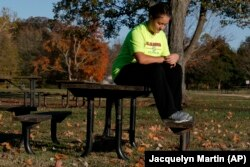 """Grace Brown, 14, adjusts her fitness tracker at the park where she does her jogging workouts for her """"online PE"""" class, in Alexandria, Va., Friday, Nov. 1, 2019."""
