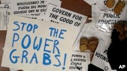 Carteles de protesta usados durante la sesión especial de la legislatura de Carolina del Norte en Raleigh, en la que se aprobaron medidas que restan poder al nuevo gobernador demócrata Roy Cooper.