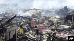 Rescuers conduct search operation amidst smoldering debris in Kesennuma, northern Japan Monday, March 14, 2011 following Friday's massive earthquake and the ensuing tsunami. (AP Photo/Yomiuri Shimbun, Miho Ikeya) JAPAN OUT, MANDATORY CREDIT