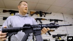 FILE – A gun shop owner in Illinois shows off an AR-15 assault rifle.