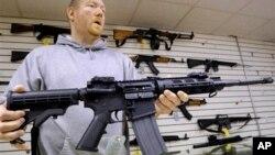 یک فروشنده سلاح در آمریکا یک اسلحه AR-15 را نشان می دهد.