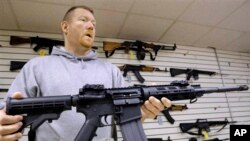 FILE - John Jackson, co-owner of Capitol City Arms Supply, shows off an AR-15 assault rifle for sale, Jan. 16, 2013, at his business in Springfield, Illinois.