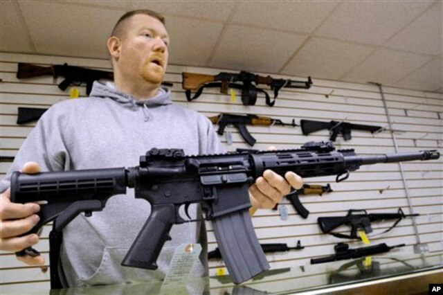 FILE - The owner of a gun shop holds one of the assault rifles his store sells.