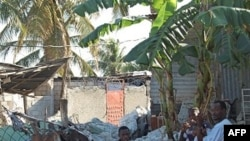 海地一家灾民继续坐在废墟上等待