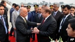 Pakistani Prime Minister Nawaz Sharif, center right, greets Afghan President Ashraf Ghani, upon his arrival at Nur Khan airbase in Rawalpindi, Pakistan, Dec. 9, 2015.