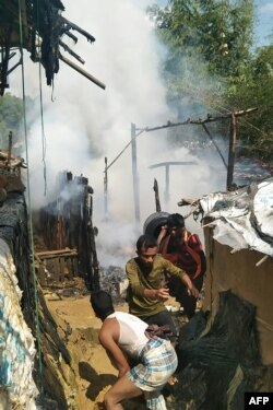 Pengungsi Rohingya mencoba memadamkan api setelah bentrokan antara geng narkoba Rohingya yang bersaing di kamp pengungsi Kutupalong di Ukhia, 7 Oktober 2020.
