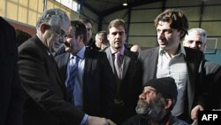 Thủ tướng Hy Lạp Lucas Papademos (trái) chào một người vô gia cư tại buổi ăn do chính quyền cung cấp cho những người vô gia cư vào ngày đầu năm