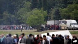 FILE - Migrants and refugees line up for food distribution at the northern Greek border point of Idomeni, Greece, May 2, 2016.