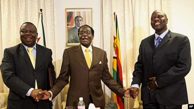 President Robert Mugabe, center, shares a light moment with Morgan Tsvangirai, left, Zimbabwe's prime minister and his deputy, Arthur Mutambara, in Harare, December 23, 2009. (file photo)